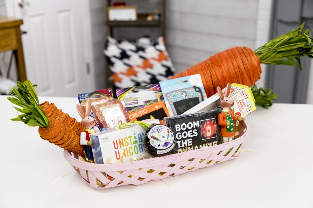 Tween Easter Basket with boogie board, pokemon cards, creatto light, crazy crayon, unstable unicorns, boom goes the dynamite, and cosmic necklace kit