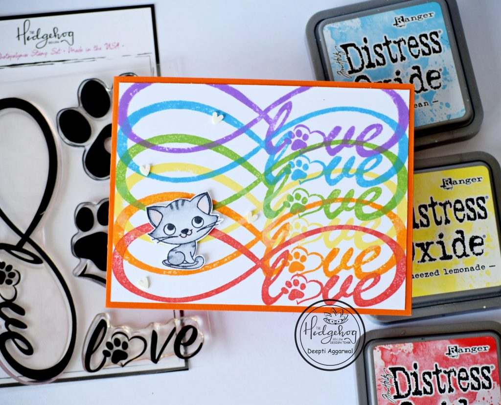 Rainbow colored love card with cat image along with supplies